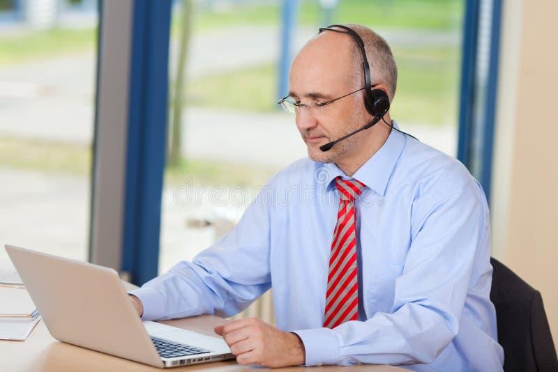 De Uitvoerende Dragende Hoofdtelefoon van de klantendienst terwijl het Gebruiken van Laptop stock afbeeldingen