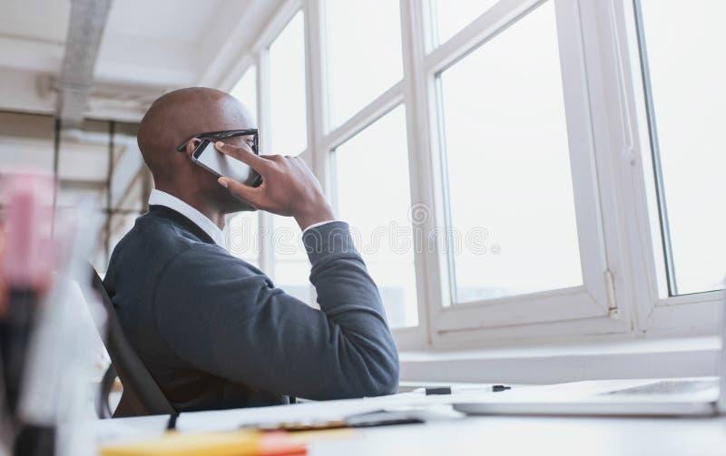 De uitvoerende macht op telefoon terwijl op het werk stock afbeeldingen