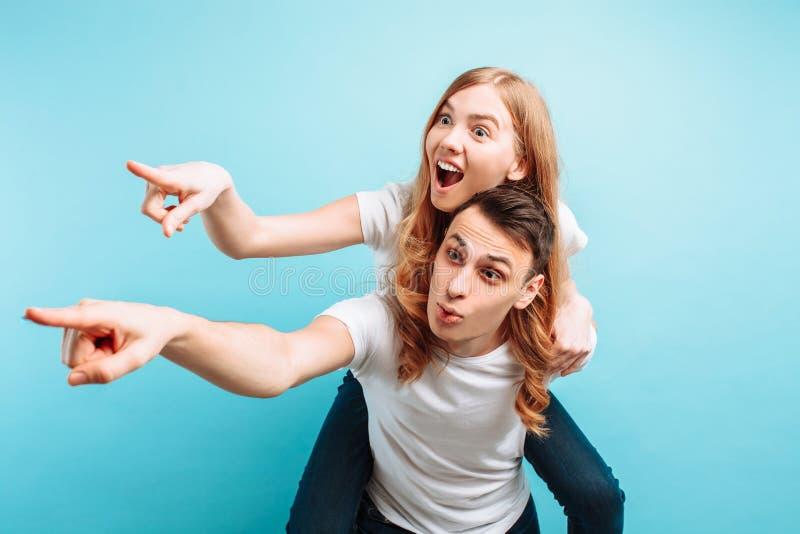 De um homem e de uma mulher, um homem que retém uma mulher no seu, apontando ao lado no copyspace, em um fundo azul fotos de stock royalty free