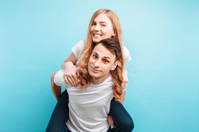 De um par de amor, com prazer, um homem leva uma mulher alegre no seu para trás, em um fundo azul imagem de stock