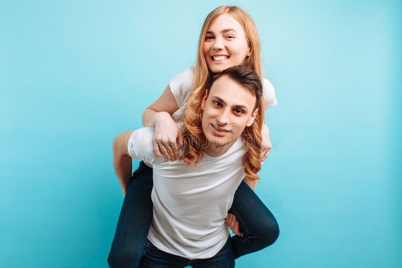 De um par de amor, com prazer, um homem leva uma mulher alegre no seu para trás, em um fundo azul fotos de stock royalty free