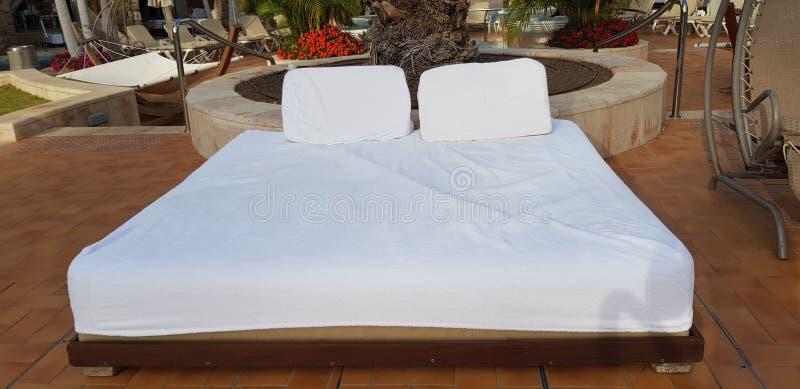 De uma cama confortável para bronzeado e do resto com colchão branco perto de uma cadeira de balanço fotografia de stock royalty free