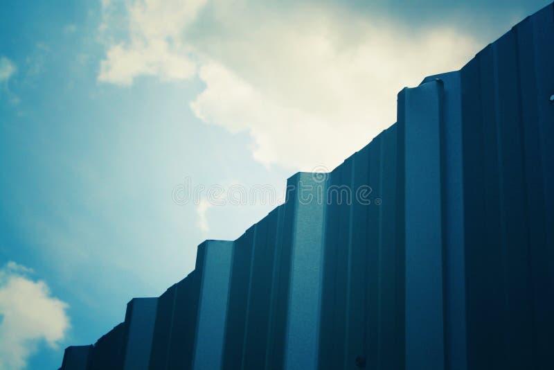 De uma parte da parede do zinco tem o céu no dia imagem de stock