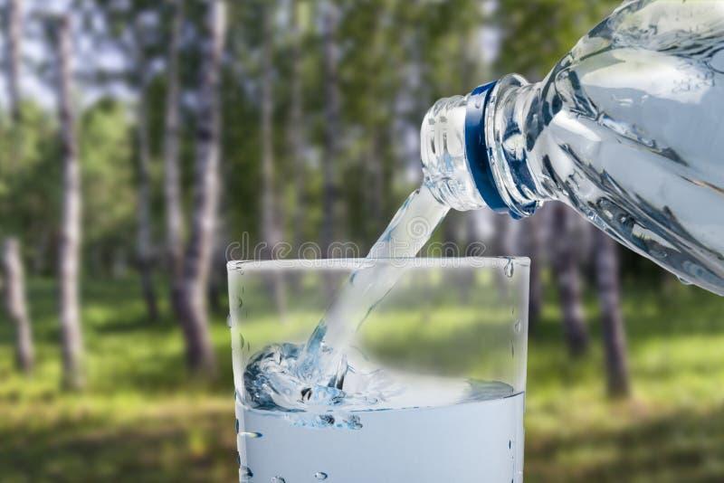 De una botella de corrientes en un vidrio en el fondo del verano del verano imagenes de archivo