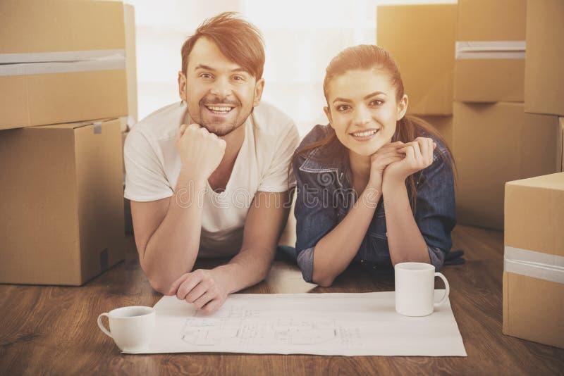 De unga lyckliga paren som planerar ett nytt hus Flytta sig köp av den nya boningen fotografering för bildbyråer