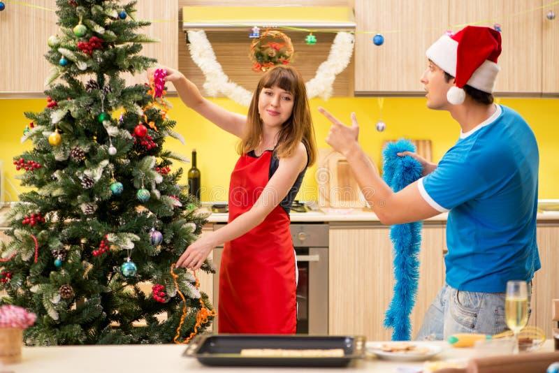 De unga paren som firar jul i kök fotografering för bildbyråer