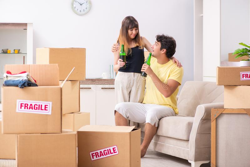 De unga paren som flyttar sig till den nya lägenheten med bräcklig saker royaltyfria bilder