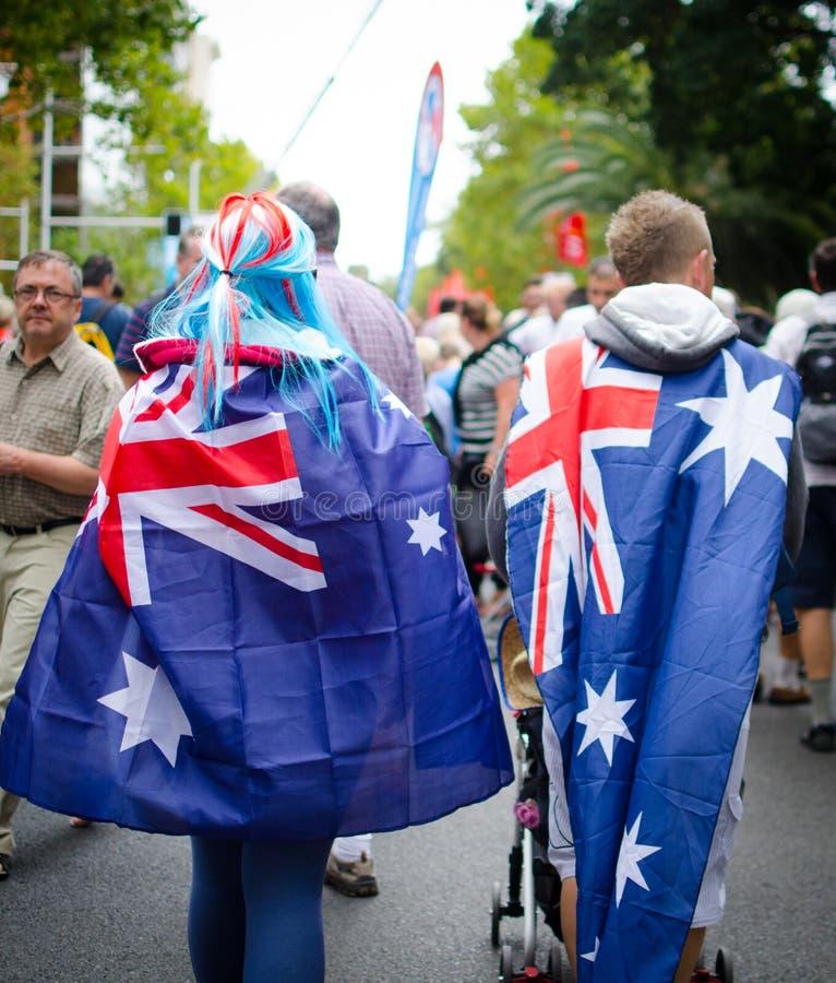 De unga paren täcker upp själva med australiska flaggor och att gå runt om stad på den Australien dagen arkivfoton