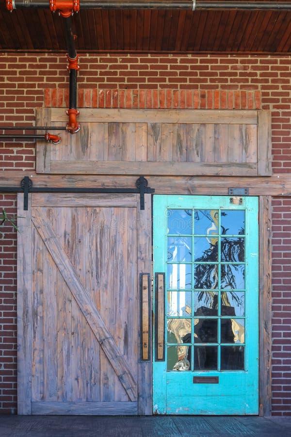 De unieke rustieke staldeuringang aan de bouw met weerspiegeling van aard in één kant met glasruiten allen plaatste in baksteen m stock foto