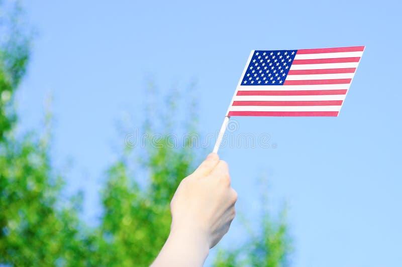 De V.S. markeren in handen tegen een blauwe duidelijke hemel en groene bomen royalty-vrije stock foto