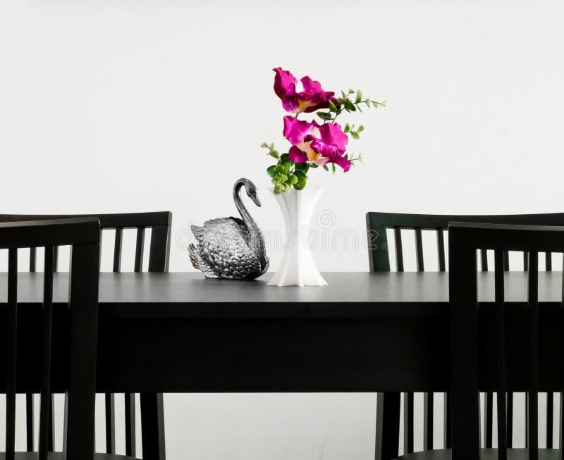 De vaas van bloem en het zilver snijden standbeeldzwaan op een lijst royalty-vrije stock foto's