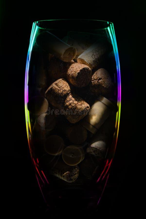 De vaas van het kristalglas met kurken van wijnflessen op donkere bac stock foto