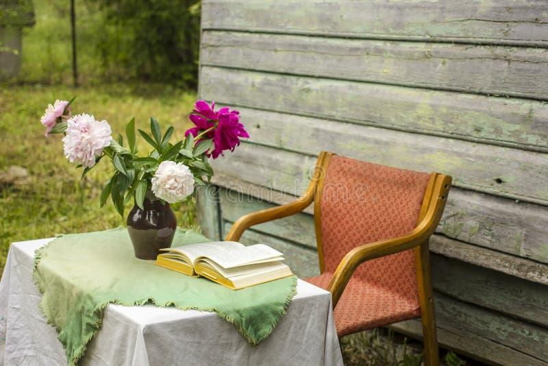 De vaas van mooie pioen en een gesloten boek op een lijst behandelden verstand royalty-vrije stock foto's