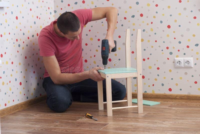 De vader assembleert een stoel voor kinderen stock foto