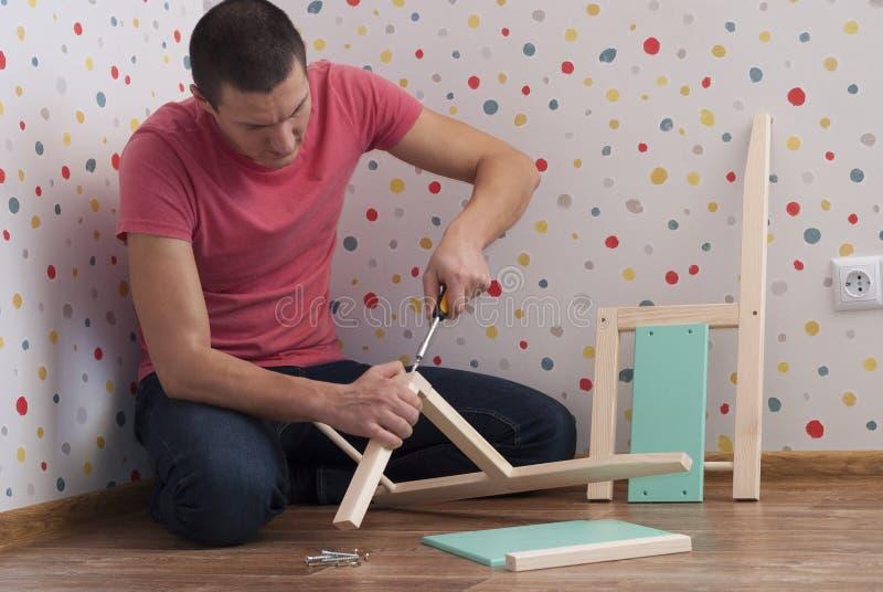 De vader assembleert een stoel voor kinderen stock afbeelding