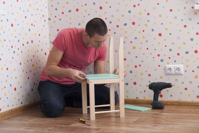 De vader assembleert een stoel voor kinderen stock foto's