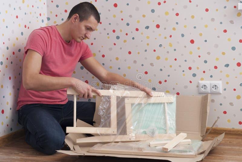 De vader assembleert een stoel voor kinderen royalty-vrije stock afbeeldingen