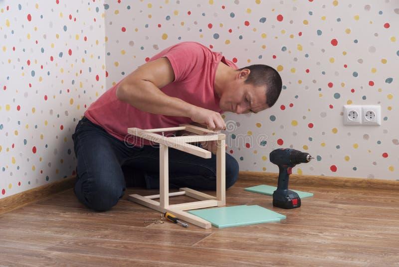 De vader assembleert een stoel voor kinderen stock fotografie
