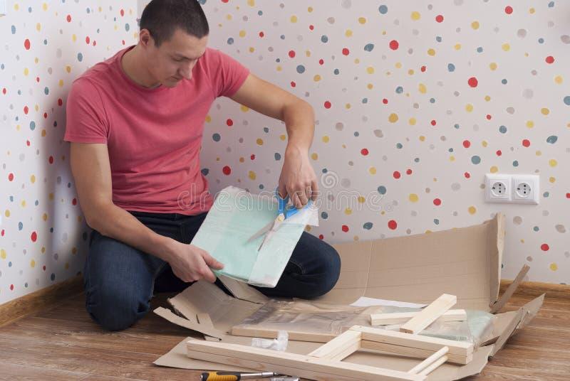 De vader assembleert een stoel voor kinderen stock afbeeldingen