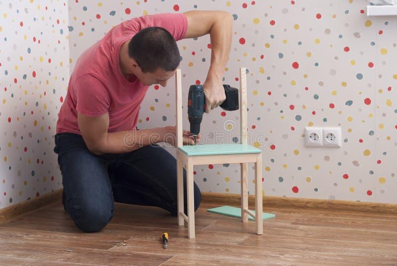 De vader assembleert een stoel voor kinderen royalty-vrije stock foto