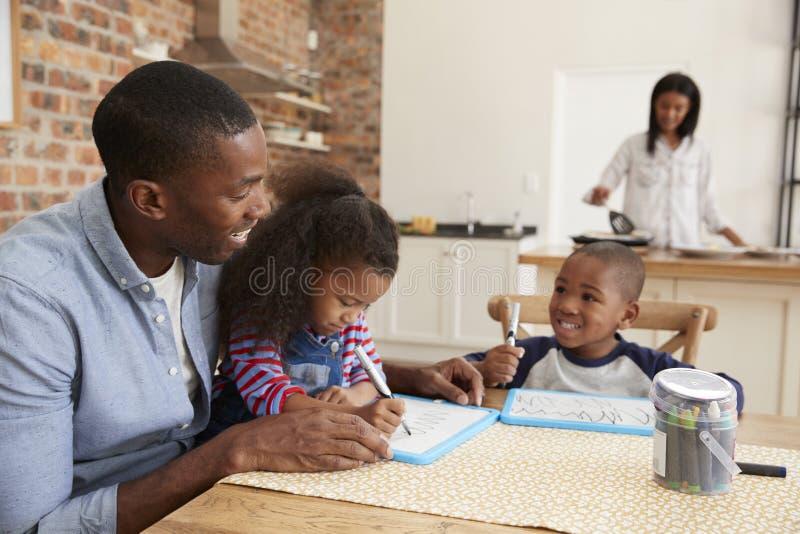 De vader And Children Drawing bij Lijst als Moeder bereidt Maaltijd voor stock fotografie