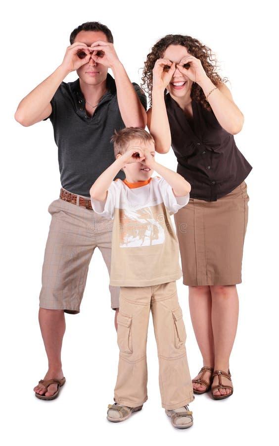 De vader, de zoon en de moeder kijken in gebied-glazen van stock foto's