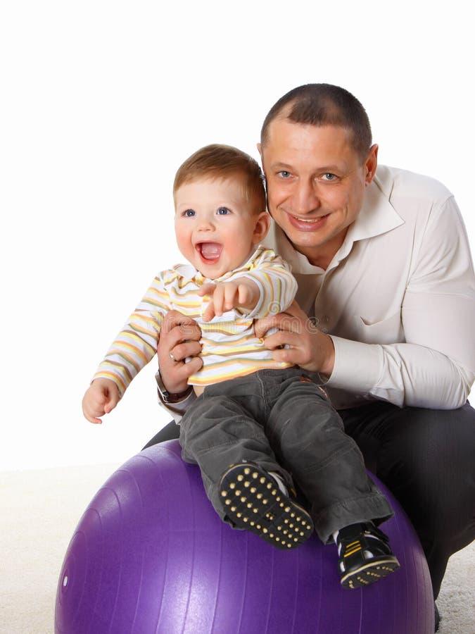 De vader die met weinig zoon op de grote bal speelt stock foto's