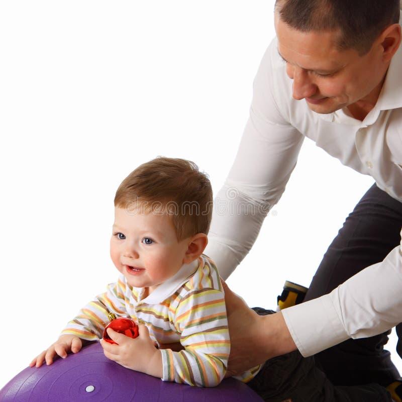 De vader die met weinig zoon op de grote bal speelt royalty-vrije stock foto's