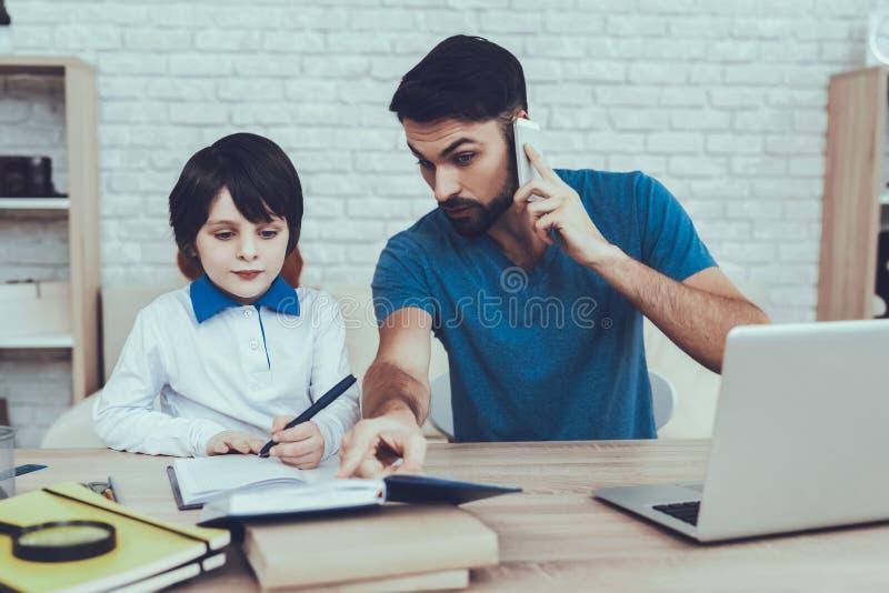 De vader doet een Thuiswerk met Zoon stock afbeeldingen