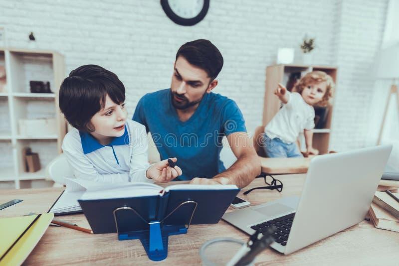 De vader doet een Thuiswerk met Zoon stock fotografie