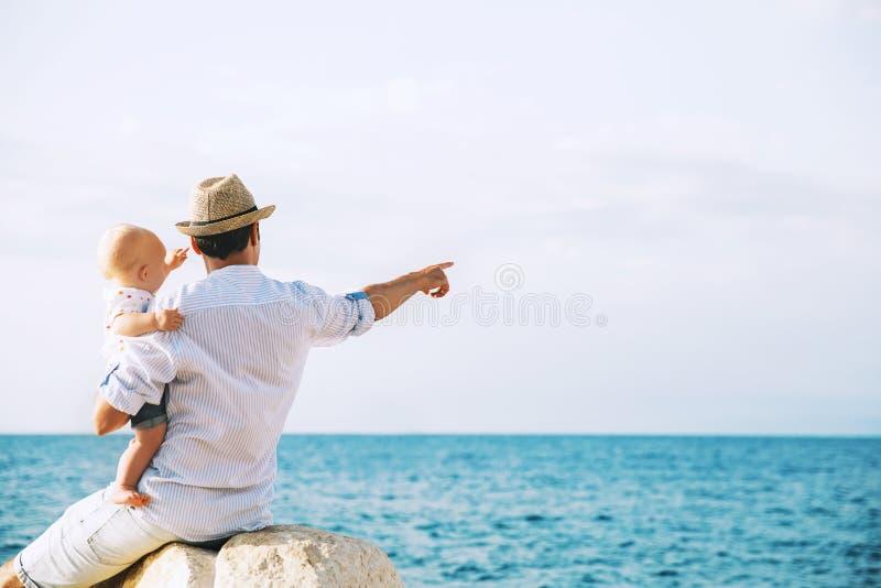 De vader en de baby zijn wijzen op op overzeese en hemelachtergronden royalty-vrije stock foto's