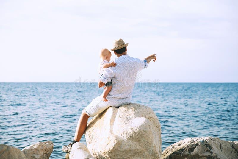 De vader en de baby zijn wijzen op op overzeese en hemelachtergronden royalty-vrije stock fotografie