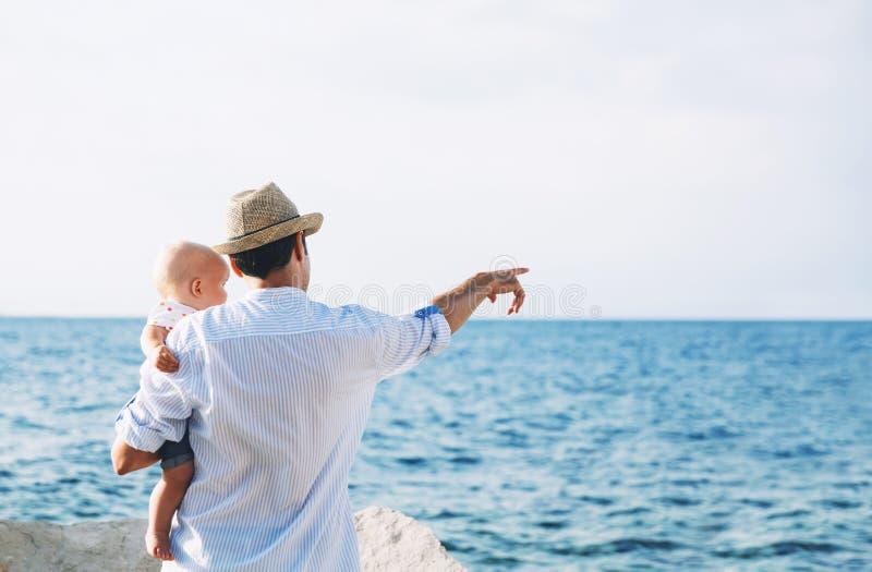 De vader en de baby zijn wijzen op op overzeese en hemelachtergronden stock fotografie