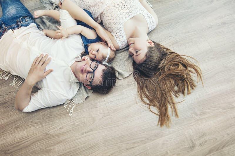 De vader en de baby van de familiemoeder zijn het gelukkige samen thuis glimlachen stock afbeeldingen