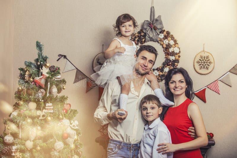 De vader en de kinderen van de familiemoeder met binnen giften in Kerstmis royalty-vrije stock afbeeldingen