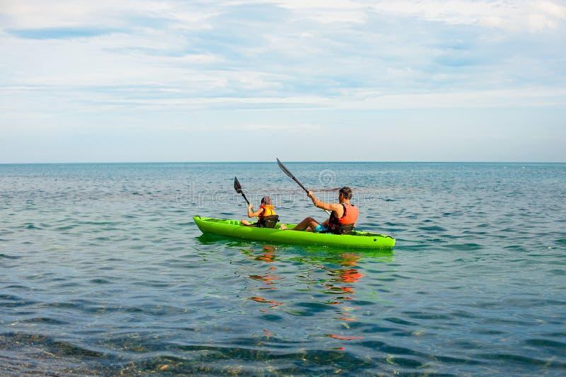 De vader en de zoon doen het kayaking bij het meer met mooie toeristen natuurlijke als achtergrond op gele kajakboot na schoon af stock foto