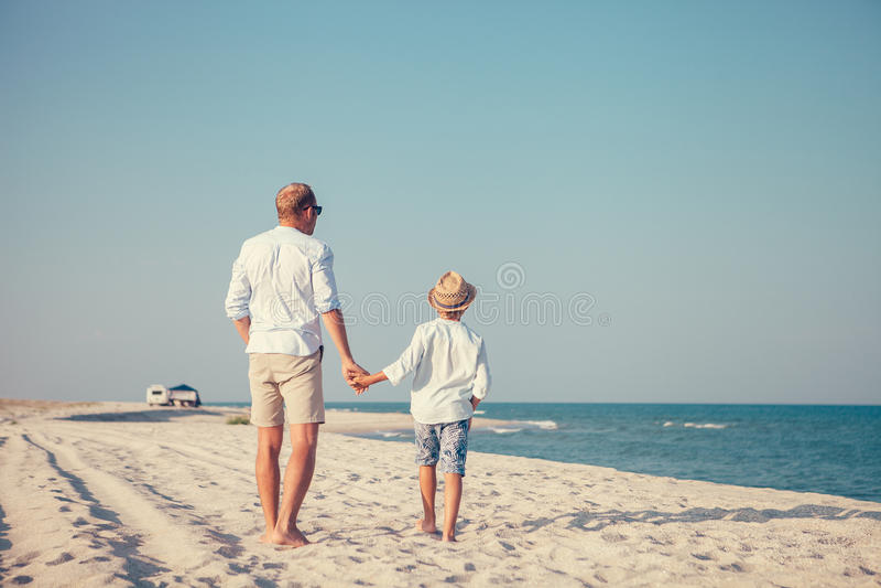 De vader en de zoon lopen op verlaten overzees strand niet verre van hun Au royalty-vrije stock afbeelding