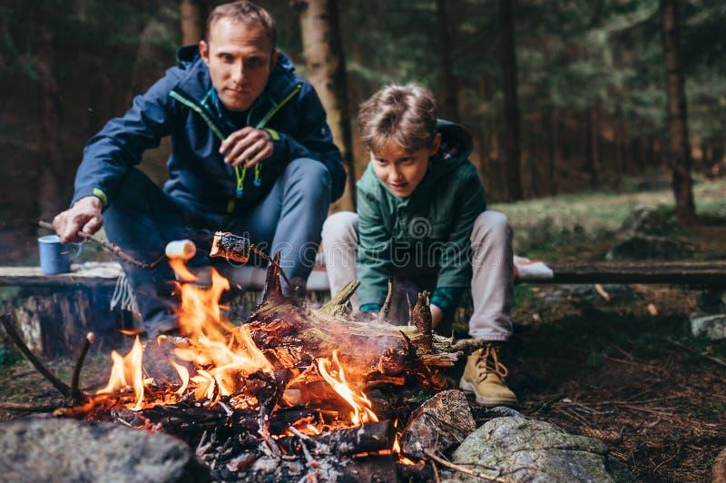 De vader en de zoon roosteren het mashmallowsuikergoed op de kampbrand royalty-vrije stock foto