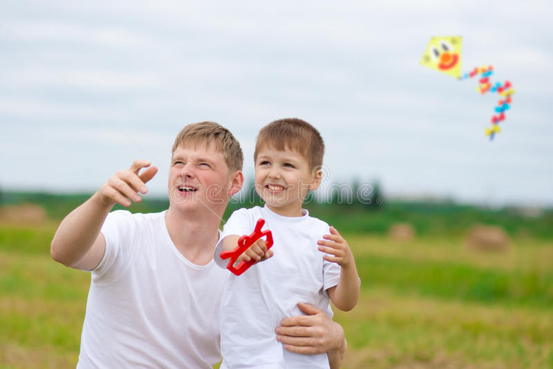 De vader en de zoon vliegen samen een vlieger in de zomer stock foto