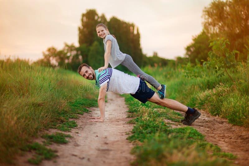 De vader en de dochter doen acrobatische oefeningen stock foto's