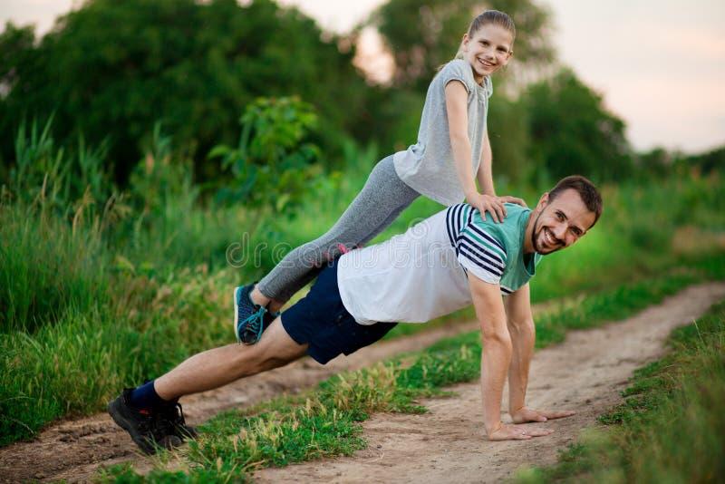 De vader en de dochter doen acrobatische oefeningen royalty-vrije stock fotografie