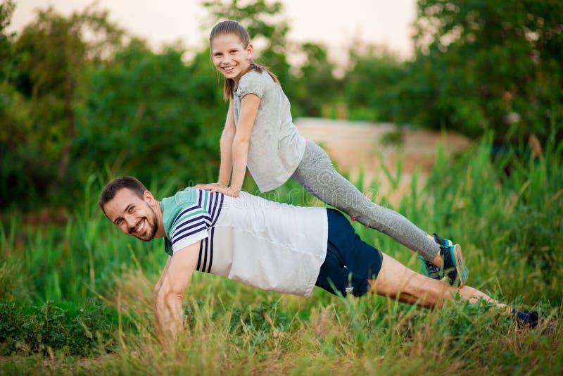 De vader en de dochter doen acrobatische oefeningen royalty-vrije stock afbeeldingen