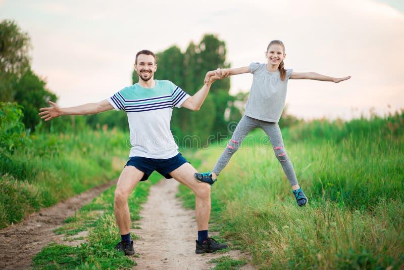 De vader en de dochter doen acrobatische oefeningen stock afbeeldingen
