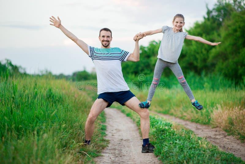 De vader en de dochter doen acrobatische oefeningen stock foto
