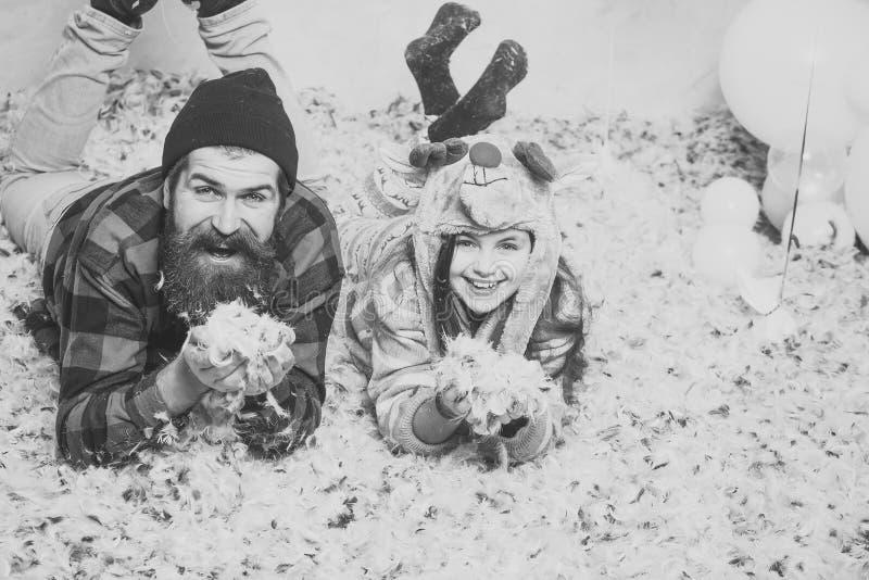De vader en de dochter liggen in veren, Kerstmis Mens hipster en kindglimlach bij Kerstmis De partij van de familievakantie Dit i stock foto's