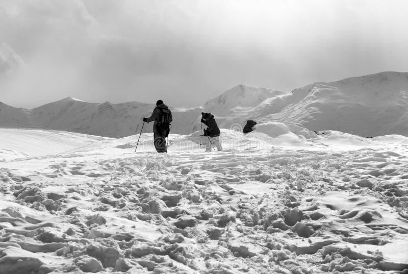 De vader en de dochter op ski nemen na sneeuwval zijn toevlucht bij zondag met grijze hemel stock afbeeldingen