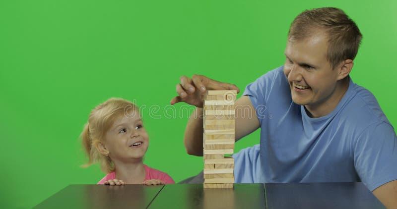 De vader en de dochter spelen jenga Weinig kind trekt houten blokken van toren stock foto