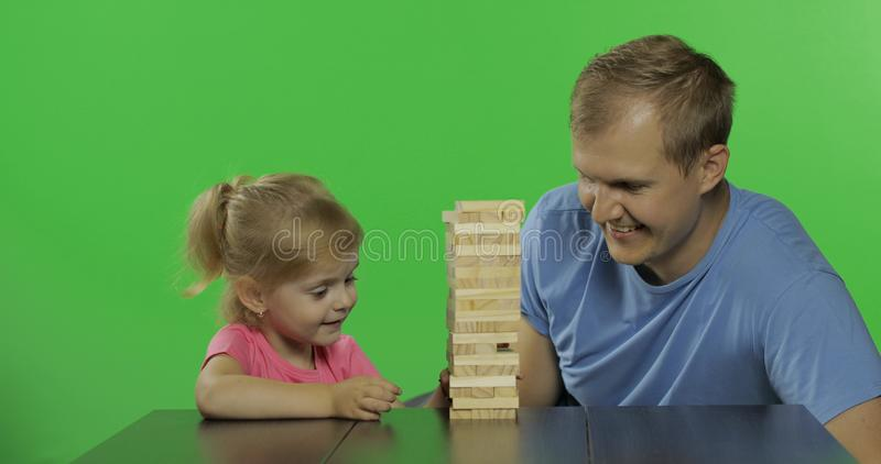 De vader en de dochter spelen jenga Weinig kind trekt houten blokken van toren royalty-vrije stock afbeelding