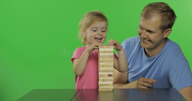 De vader en de dochter spelen jenga Weinig kind trekt houten blokken van toren royalty-vrije stock foto's