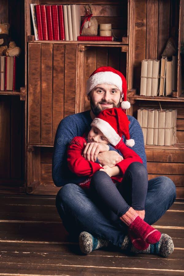 De vader en de dochter zitten op de vloer die en op Kerstmis omhelzen wachten stock afbeeldingen